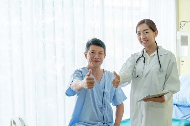 Asian senior patient on hospital bed discussing with female doctor