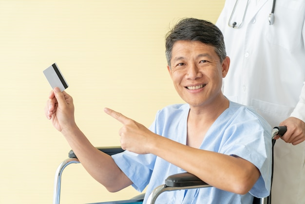 Asian senior patient wheelchair smiling with credit card