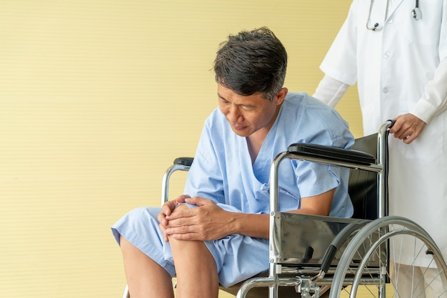 Asian senior patient wheelchair with knee pain