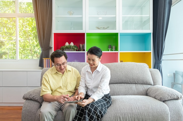Asian senior people, grand parents using digital tablet in the home