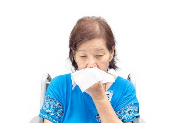 손수건으로 코를 푸는 아시아 노인 여성