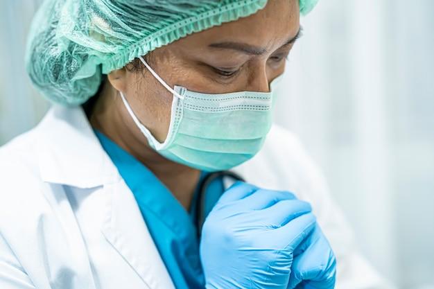 Covid-19 코로나 바이러스를 보호하기 위해 얼굴 마스크와 ppe 정장을 입고 아시아 수석 여자 의사.