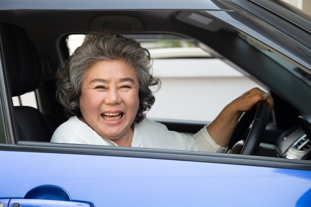 Asian senior woman driving a car and smile happily with glad positive expression during the drive to travel journey, people enjoy laughing transport and drive thru concept