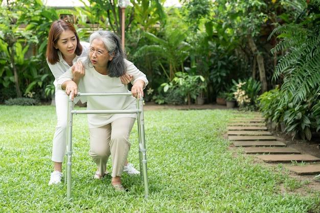 裏庭で家に倒れるアジアの年配の女性