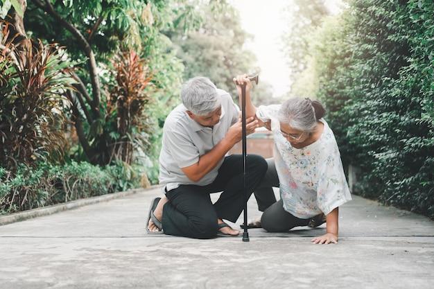 문앞에서 비틀거리고 고통에 울고 그녀의 남편이 지원을 돕기 위해 온 후 집에서 누워있는 바닥에 쓰러진 아시아 노인 여성. 오래 된 노인 보험 및 건강 관리의 개념