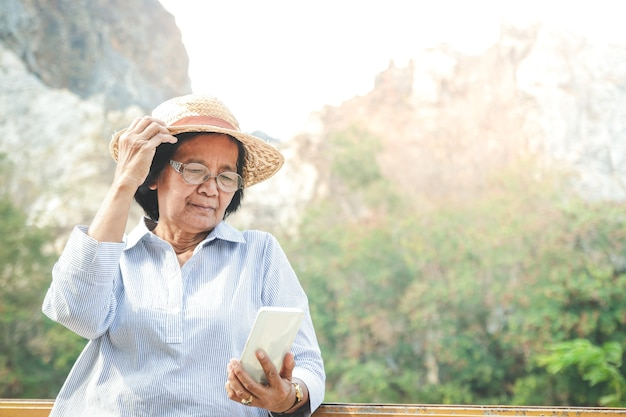 スマートフォンを持って写真を撮り、ソーシャルメディアで遊んでいるアジアの年配の女性は、退職後の生活を楽しんでいます。高齢者コミュニティの概念。コピースペース