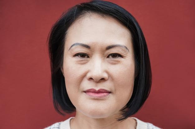 屋外でカメラを見ているアジアの年配の女性-顔に焦点を当てる