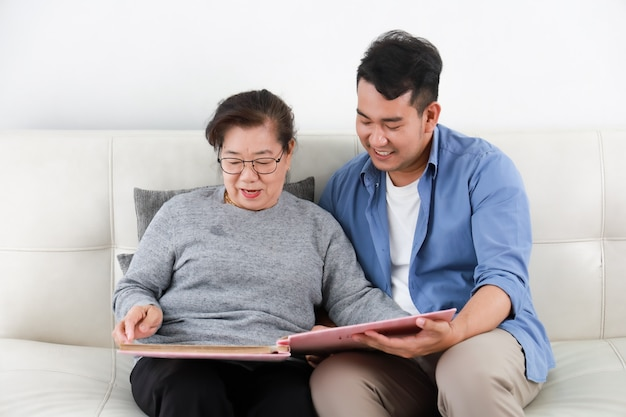Asian senior woman mother and young man son in blue shirt looking photo album and talking happy smile face  in living room