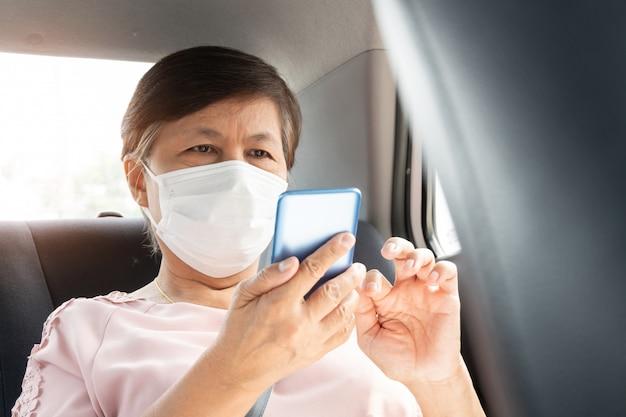 자동차에 앉아있는 동안 스마트 폰을 사용하여 코로나 바이러스 또는 covid-19를 방지하기 위해 아시아 수석 여자 승객 착용 수술 용 마스크.