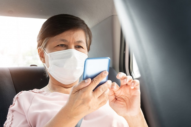 Asian senior woman passenger wear surgical mask for prevent coronavirus or covid-19 using smartphone while sitting in car.