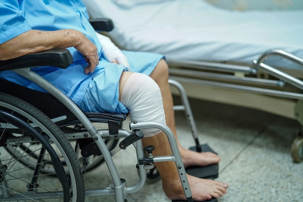 Asian senior woman patient accident at knee with bandage on wheelchair in hospital.
