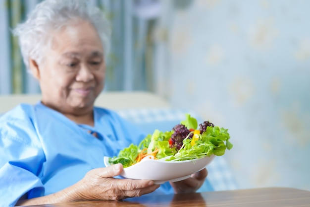 Asian senior woman patient eating breakfast in hospital.