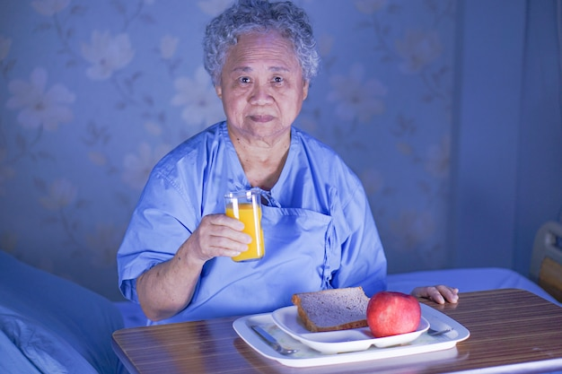 Asian senior woman patient eating breakfast in hospital