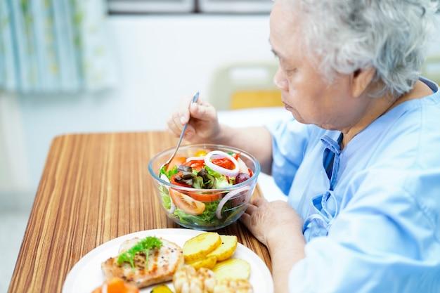 病院のベッドで朝食を食べるアジアの年配の女性患者。