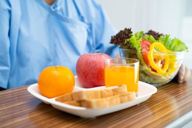 病院で朝食野菜の健康食品を食べるアジアの年配の女性患者