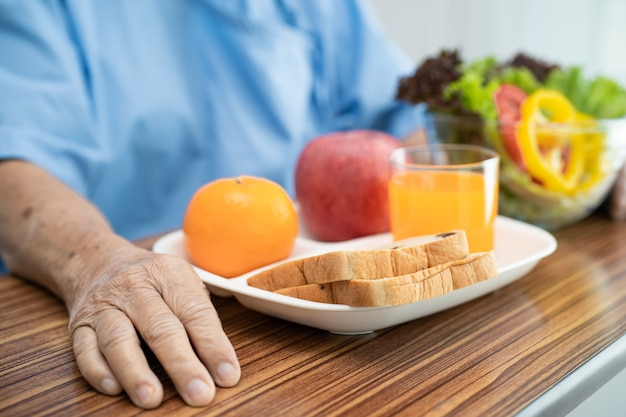 Asian senior woman patient eating breakfast vegetable healthy food