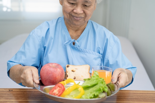 朝食野菜健康食品を食べるアジアの年配の女性患者