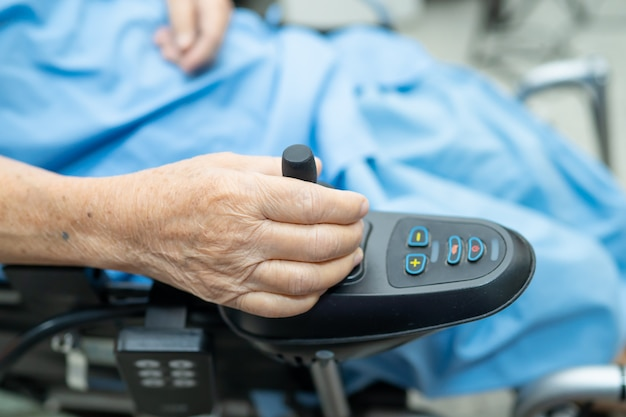 Asian senior woman patient on electric wheelchair with remote control at hospital.