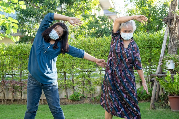 公園で幸せな新鮮な楽しみとアジアの年配の女性患者の運動