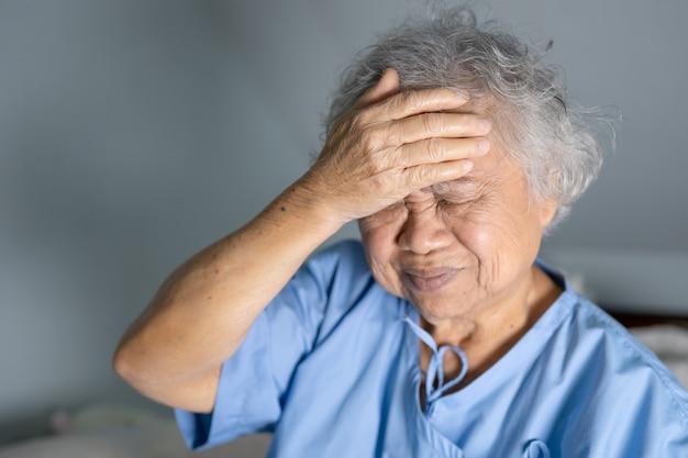 Asian senior woman patient headache in hospital.
