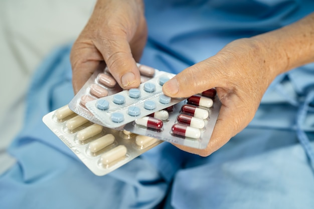 Asian senior woman patient holding antibiotics capsule pills in blister packaging for treatment