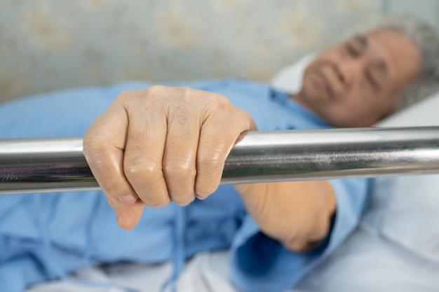 Asian senior woman patient lie down handle the rail bed in hospital.