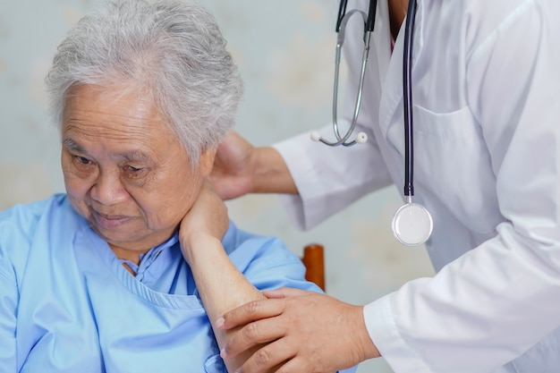 Asian senior woman patient neck pain while sitting  in hospital.