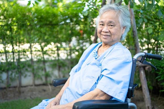 Азиатская старшая женщина-пациент на инвалидной коляске в парке здоровая сильная медицинская концепция