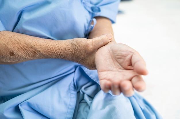 Азиатская старшая женщина пациент боли рукой и запястье
