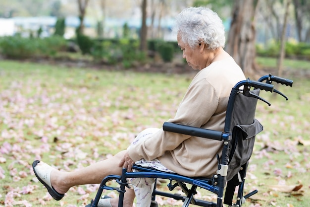 Asian senior woman patient pain her knee on wheelchair in park.