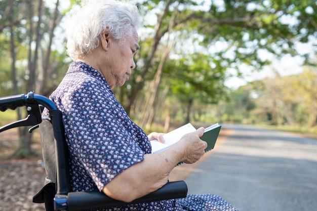공원에 앉아있는 동안 책을 읽고 아시아 고위 여자 환자