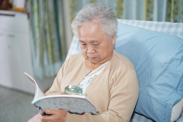 Asian senior woman patient reading a book while sitting on bed in hospital.
