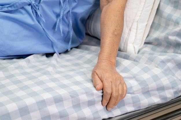 病院のベッドの上に座っているアジアの年配の女性患者。