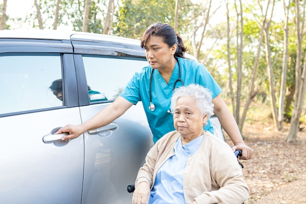 Asian senior woman patient sitting on wheelchair prepare get to car.