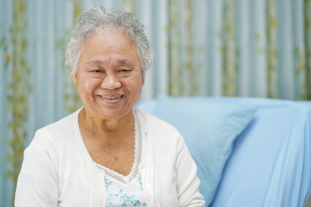 Asian senior woman patient smile bright face while sitting on bed in hospital.