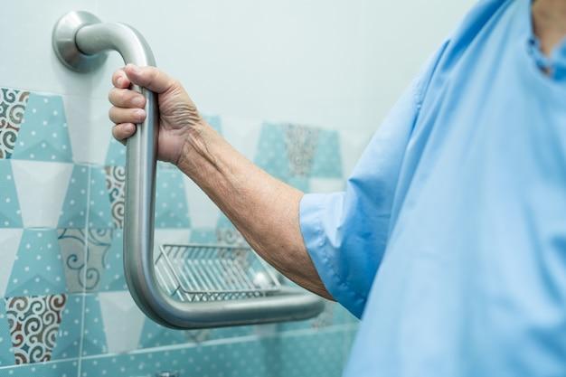 Азиатская женщина пожилого возраста использует ручку безопасности с помощником по поддержке в больнице