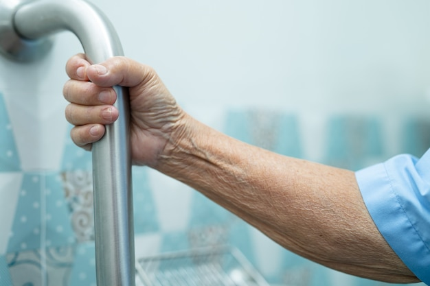 Asian senior woman patient use slope walkway handle security