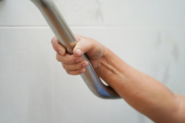 Asian senior woman patient use toilet bathroom handle security in hospital.