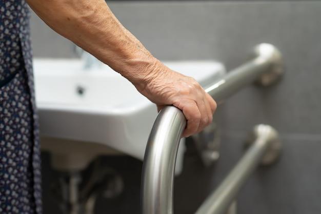 アジアの年配の女性患者が病院でトイレのバスルームハンドルセキュリティを使用します。