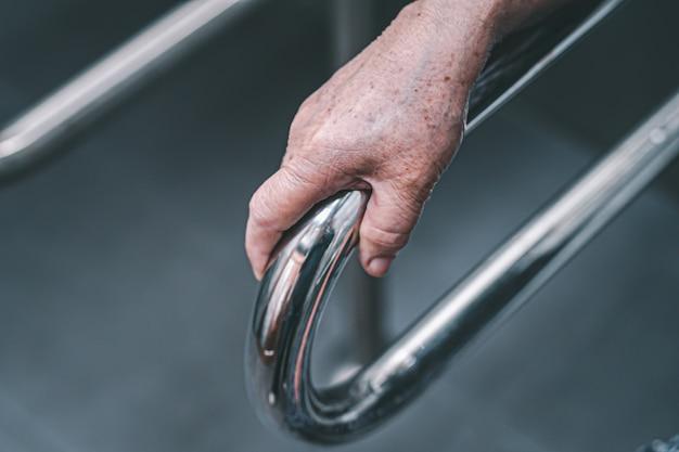 アジアの年配の女性患者は病院でトイレのバスルームハンドルセキュリティを使用します。
