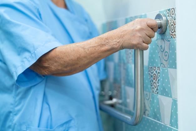 アジアの年配の女性患者は病院でトイレのバスルームハンドルセキュリティを使用します