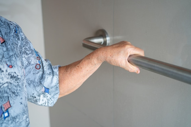アジアの年配の女性患者が看護病棟でトイレバスルームハンドルセキュリティを使用