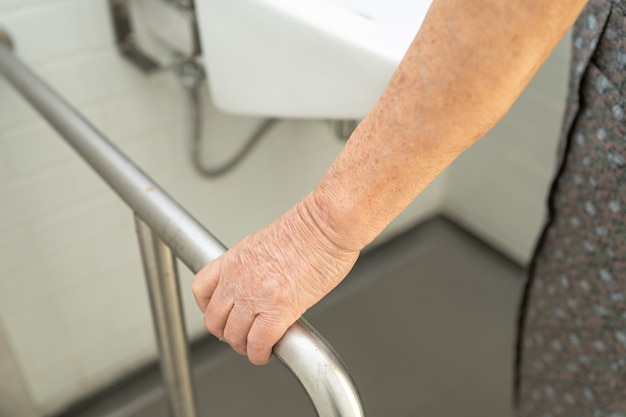 Безопасность ручки ванной комнаты туалета ванной комнаты азиатской пожилой женщины пациента в больнице медсестер