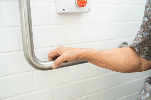 アジアの年配の女性患者はトイレバスルームハンドルセキュリティを使用します。