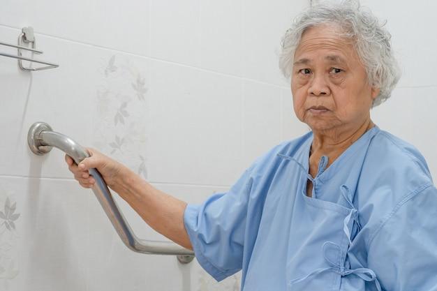 アジアの年配の女性患者はトイレの浴室のハンドルのセキュリティを使用します。