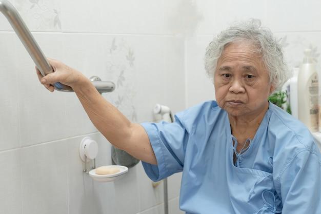 アジアの年配の女性患者はトイレの浴室のハンドルのセキュリティを使用します