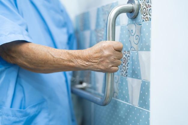アジアの年配の女性患者はトイレのバスルームハンドルのセキュリティを使用します