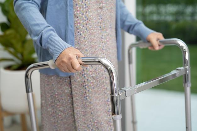 アジアの年配の女性患者が看護病院で歩行器と一緒に歩く健康的な強力な医療概念