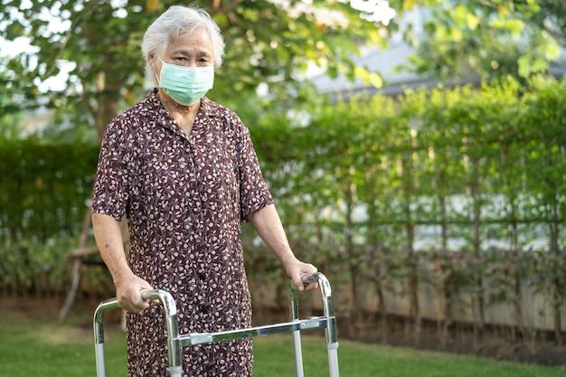 アジアの年配の女性患者が公園で歩行者と一緒に歩く健康的な強力な医療コンセプト