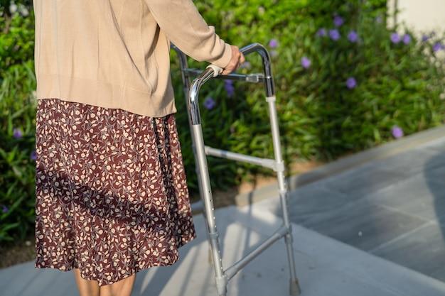 アジアの年配の女性患者が公園で歩行者と一緒に歩く
